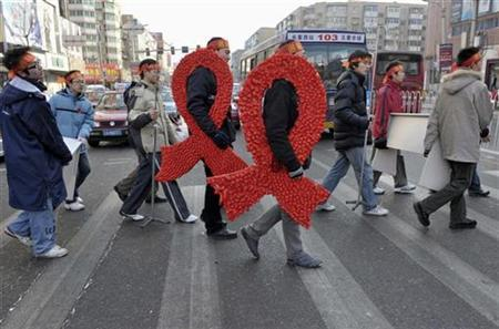 University students carry large red ribbons on a street during an HIV/AIDS awareness rally ahead of World AIDS day in Shenyang, Liaoning province November 29, 2008. REUTERS/Stringer