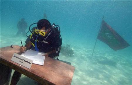 Maldives President Mohamed Nasheed signs a declaration during the first underwater cabinet meeting in the Maldives, October 17, 2009. The Maldivian president and ministers held the world's first underwater cabinet meeting on Saturday, in a symbolic cry for help over rising sea levels that threaten the tropical archipelago's existence. REUTERS/Maldives Government/Handout