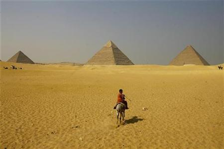 A boy rides a horse in front of the Great Pyramids of Giza on the outskirts of Cairo, October 12, 2009. REUTERS/Marko Djurica