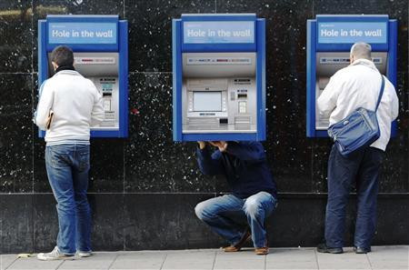 A man repairs a cash machine outside a bank in London, November 25, 2009. REUTERS/Luke MacGregor