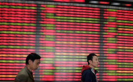 Investors walk past an electronic board at a stock exchange market in Shanghai March 13, 2007. REUTERS/Aly Song