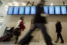 <p>Holiday travelers pass by a row of arrival and departure screens at Hartsfield-Jackson International Airport in Atlanta, Georgia, November 25, 2009. REUTERS/Tami Chappell</p>