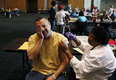 Michael Hindman (L) reacts as the nurse pulls his sleeve up to administer a shot of the H1N1 flu vaccination in Arlington, Texas November 24, 2009. REUTERS/Jessica Rinaldi