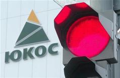 <p>Логотип нефтяной компании ЮКОС на здании в Нефтеюганске 26 июля 2004 года. Бывшие владельцы ЮКОСа заявили во вторник о получении постановления суда, позволяющего подать иск к руководству РФ с требованием выплатить до $100 миллиардов из-за национализации некогда крупнейшей российской нефтяной компании. REUTERS/Sergei Karpukhin</p>