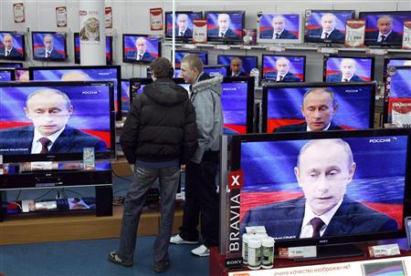 Men look at a television screening of Russia's Prime Minister Vladimir Putin as he speaks during a question-and-answer show at a Russian state TV channel, at an electronics shop in Moscow, December 3, 2009. REUTERS/Denis Sinyakov