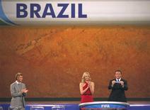 <p>Secretário-geral da Fifa, Jerome Valcke, sorteia o nome do Brasil como cabeça-de-chave do Grupo G da Copa do Mundo de 2010, ao lado de David Beckham e da atriz sul-africana Charlize Theron REUTERS/Mike Hutchings</p>