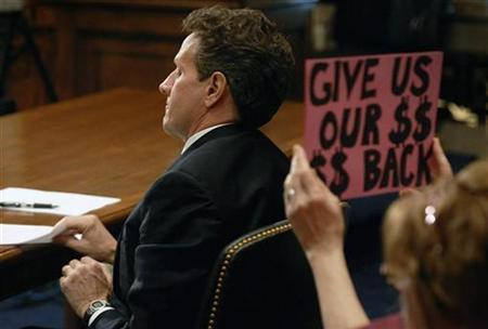 A protester holds a sign as Treasury Secretary Timothy Geithner addresses a hearing of the Congressional Oversight Panel of the Troubled Asset Relief Program on Capitol Hill in this April 21, 2009 file photo. REUTERS/Jonathan Ernst