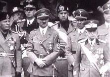 <p>King Victor Emanuel III, (R) Adolf Hitler (C) and Benito Mussolini (L) watch fascist troops march past from a balcony in central Rome in this 1941 television file footage. REUTERS/Reuters TV</p>