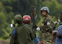 <p>A peacekeeper watches Democratic Republic of Congo soldiers on motorbike ride past, December 4, 2008. REUTERS/Peter Andrews</p>