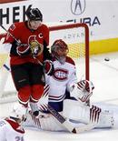 <p>Ottawa Senators' captain Daniel Alfredsson jumps to avoid a shot on Montreal Canadiens' goalie Jaroslav Halak during the third period of their NHL game in Ottawa December 8, 2009. REUTERS/Blair Gable</p>