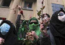 <p>Student supporters of opposition leader Mirhossein Mousavi hold red roses during protests in central Tehran December 7, 2009. REUTERS/via Your View</p>
