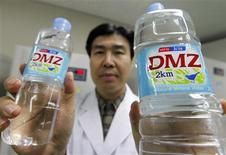 <p>A manager of bottler Login Beverage poses with bottled water at a factory of the company in Yeoncheon near the demilitarized zone (DMZ) separating the two Koreas, northeast of Seoul, December 9, 2009. REUTERS/Lee Jae-Won</p>