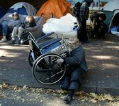 <p>A squatter camped outside an empty building in Vancouver's rundown eastside lifts his wheelchair over the high curb of the sidewalk October 30, 2002. REUTERS/Andy Clark</p>
