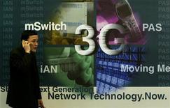 """<p>Посетитель выставки ITU telecom Asia 2002 говорит по телефону напротив рекламы сервисов 3G в Гонконге 2 декабря 2002 года. Все три оператора """"Большой тройки"""" - МСТ, ВымпелКом и МегаФон - получили разрешение Роскомнадзора на использование частот, необходимых для работы сети третьего поколения 3G вне помещений на территории Москвы, сообщили компании в понедельник. REUTERS/Bobby Yip</p>"""