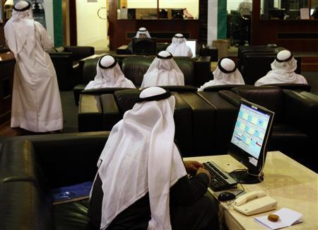 Investors look at stock exchange information at the Dubai Financial Market, December 14, 2009. REUTERS/Mosab Omar