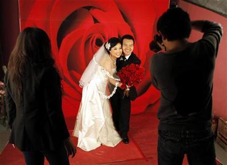 An engaged Chinese couple pose for their wedding photographs at a studio in central Beijing November 27, 2009. REUTERS/David Gray