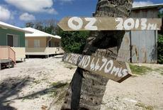 <p>Указатель с расстоянием до Новой Зеландии на стволе пальмы в деревне Анаоэ на острове Науру 11 сентября 2001 года. Науру - крошечный остров в Тихом океане - во вторник стал четвертым государством, признавшим суверенный статус Абхазии, отколовшейся от Грузии в прошлом году. REUTERS/Mark Baker</p>