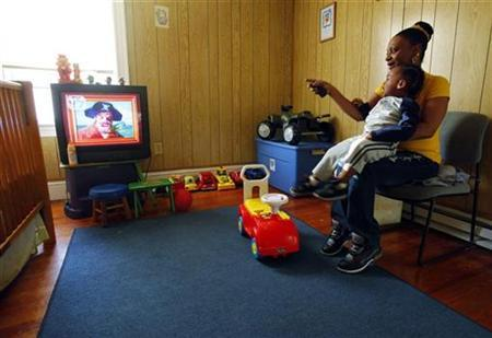 April Metts and her two-year old son Jamar watch television at her apartment in Providence, Rhode Island November 18, 2009. REUTERS/Brian Snyder
