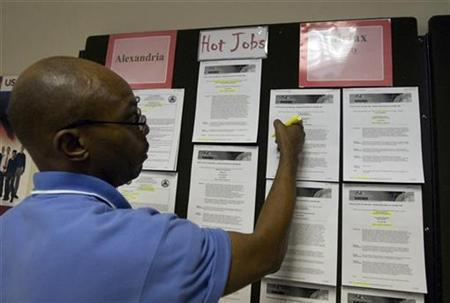 Gary Simpson, an employee at the Virginia Employment Commission office, posts job postings at the office in Alexandria, Virginia November 6, 2009. REUTERS/Molly Riley