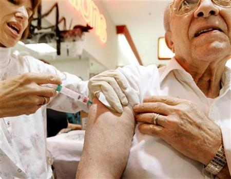 Nurse Tanis Mittelman (L) administers a flu vaccine during a clinic at the Giant food market in Fairfax, Virginia, October 13, 2004. REUTERS/Larry Downing