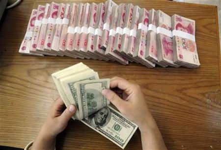 An employee counts U.S. dollar banknotes at a Bank of China branch in Hefei, Anhui province October 16, 2009. REUTERS/Stringer