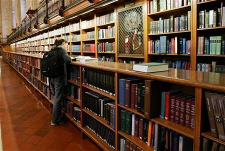 A woman stands among the bookshelves in the main reading room of The New York Public Library, December 14, 2004. REUTERS/Mike Segar MS