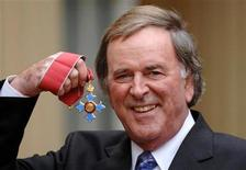 <p>Irish-born broadcaster Terry Wogan holds his OBE award (Officer of the Order of the British Empire) at Buckingham Palace in London December 6, 2005.REUTERS/Fiona Hanson/PA/WPA Pool</p>