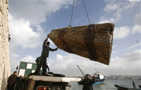 Workers direct the retrieval of an ancient Egyptian granite tower that was found in the Mediterranean Sea, at Alexandria's eastern harbour December 17, 2009. REUTERS/Asmaa Waguih