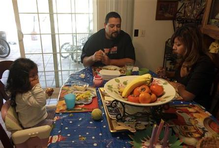 Thelma Zambrano eats lunch with her husband Jesse Torres and daughter Vida Torres, 2, at their home in Santa Ana, California, December 10, 2009. REUTERS/Lucy Nicholson