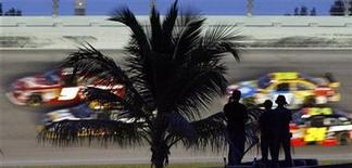 <p>Spectators watch from the roof of a truck in the infield as drivers streak past during the Ford 400 NASCAR race at Homestead-Miami Speedway in Homestead, Florida November 22, 2009. REUTERS/Hans Deryk</p>