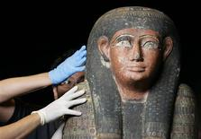 <p>Conservators inspect a sarcophagus which contained the mummy of Nekhet-iset-aru before its installation at the National Museum in Singapore December 18, 2009. REUTERS/Vivek Prakash</p>