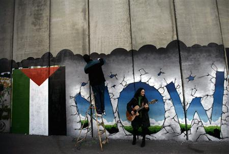 A tourist from Italy plays guitar as another sprays paint on the controversial Israeli barrier in the West Bank town of Bethlehem December 23, 2009. Christian visitors coming to Bethlehem this week to celebrate the birth of Christ will encounter a concrete wall with watchtowers, built by Israel between nearby Jerusalem and the Church of the Nativity. REUTERS/Ammar Awad