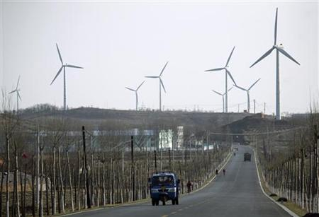 A vehicle drives past a wind power plant in Donggang, Liaoning province November 28, 2009. REUTERS/Jacky Chen