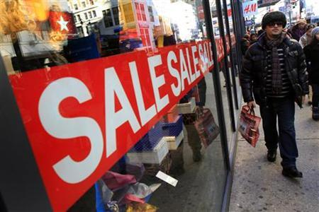 A holiday shopper passes a sale sign at a clothing store in New York December 23, 2009. REUTERS/Mike Segar