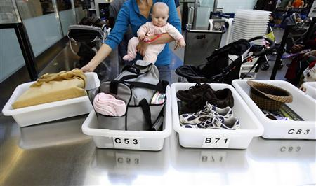 A passenger holding her baby prepares to go through a security checkpoint at Los Angeles International Airport December 29, 2009. REUTERS/Mario Anzuoni
