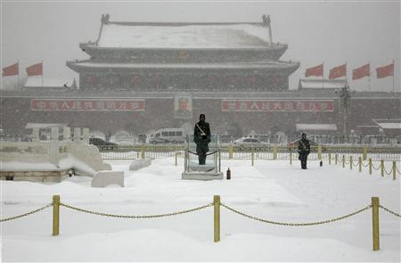 Paramilitary policemen stand guard in front of the late Chairman Mao Zedong on a snow-covered Tiananmen Square in Beijing January 3, 2010. REUTERS/David Gray