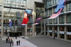 """<p>People stand under a LED screen art installation called """"Travesias"""" by Spanish artist Daniel Canogar at the European Council building in Brussels January 5, 2010. REUTERS/Thierry Roge</p>"""
