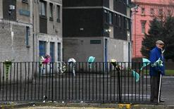 <p>A man stands next to flowers tied to a railing in memory of a man murdered by gang members in the Gorbals area of Glasgow, Scotland in this file photo dated January 4, 2010. REUTERS/David Moir</p>