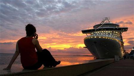 A woman talks on her phone while watching the sun set behind a cruise ship used to house attendees to the Summit of the Americas in Port of Spain, Trinidad April 18, 2009. REUTERS/Kevin Lamarque