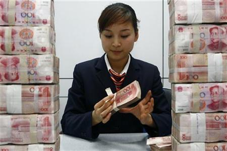 An employee counts Renminbi banknotes at a local commercial bank in Suining, Sichuan province April 9, 2009. REUTERS/Stringer
