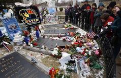 <p>Admiradores colocan flores sobre la tumba del cantante Elvis Presley en su mansión Graceland en Menphis, EEUU, ene 8 2010. Cientos de seguidores de Elvis Presley afrontaron el viernes la nieve y temperaturas bajo cero para celebrar el cumpleaños 75 de la leyenda del rock 'n' roll en su refugio de Graceland, parte de una maquinaria de marketing que genera más de 50 millones de dólares año. REUTERS/Nikki Boertman</p>