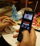 <p>Foto d'archivio. Un uomo guarda la tv in un fast food di Tokyo. REUTERS/Kim Kyung-Hoon</p>