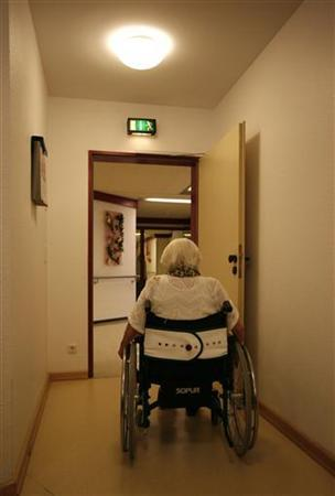 A woman in a wheelchair leaves a therapy session for residents affected by dementia at a home for the elderly in Hamburg July 14, 2009. REUTERS/Christian Charisius
