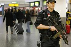 <p>Вооруженный полицейский патрулирует пассжирский терминал британского аэропорта Гэтвик 28 декабря 2009 года. Неуправляемому пассажиру одной из авиакомпаний США, чьи пьяные выходки на прошлой неделе вынудили пилотов совершить экстренную посадку в сопровождении истребителей, предъявлено обвинение в создании помех экипажу. REUTERS/Luke MacGregor</p>