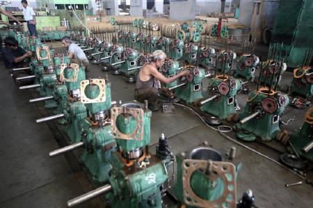 Technicians work on engines used for water pumps inside a manufacturing unit in Rajkot, 216 km (134 miles) west of Ahmedabad, in this July 2009 file photo.  REUTERS/Amit Dave