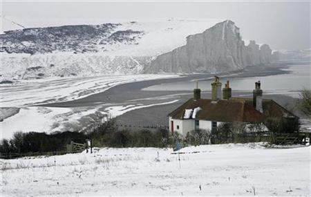 Fallen snow surrounds cottages in front of the Seven Sisters cliffs near Eastbourne in southeast England January 11, 2010. REUTERS/Luke MacGregor