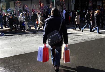 A holiday shopper carries bags through Herald Square in New York December 23, 2009. REUTERS/Mike Segar