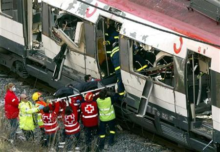 Red Cross helpers lift a body bag containing the victim of a bomb blast from a train about one kilometer outside the main train station in Madrid, March 11, 2004. REUTERS/Kai Pfaffenbach