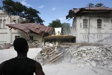 <p>Un residente local observa el traslado de los restos del palacio nacional tras un terremoto en Puerto Príncipe, ene 13 2010. El devastador terremoto en Haití es, hasta el momento, el mayor desastre natural en la era Twitter y la respuesta en el sitio de mensajería por internet ha sido crucial. REUTERS/Eduardo Munoz</p>