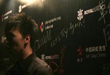 """<p>Участник конкурса красоты """"Мистер Гей Китая"""" стоит рядом с постером, Пекин 15 января 2010 года. Пекинская полиция в пятницу закрыла первый конкурс красоты среди геев в Китае, заявив, что у организаторов нет лицензии на его проведение. REUTERS/Jason Lee</p>"""